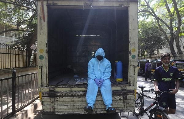 A_civic_worker_rest_on_the_back_of_a_vehicle_after_sanitizing_a_building_in_Mumbai